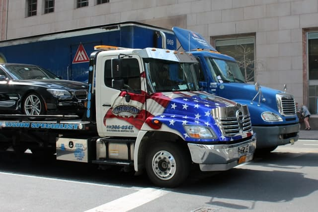 A tow truck with the American flag carries a vehicle.