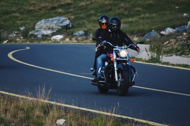 A motorcycle driver and a guest passenger ride on a bike.