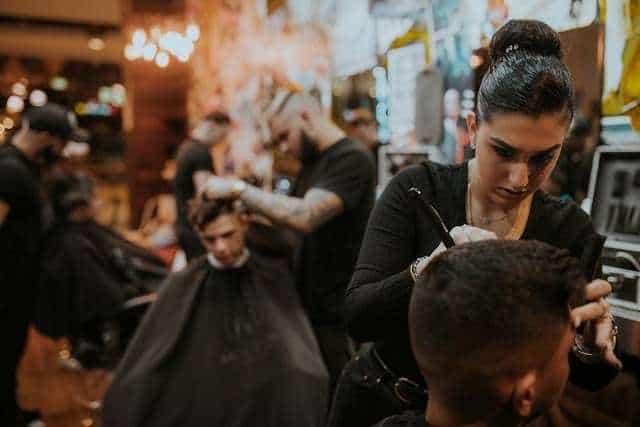 A woman cutting a man's hair at a barber shop.
