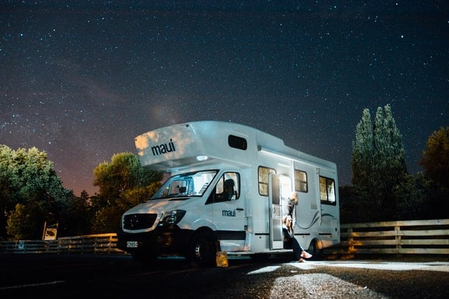 A white campervan parked under a starry sky.