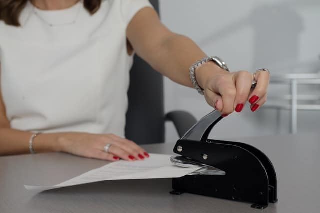 A female notary puts a seal on a legal document.