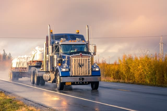 A blue truck driving on the road.